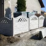 Betonový plot obklopující rodinný dům.