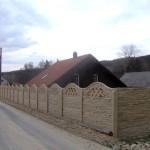 Zdobený betonový plot kolem chalupy.