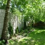 Zeleň obklopená plotem z betonu.